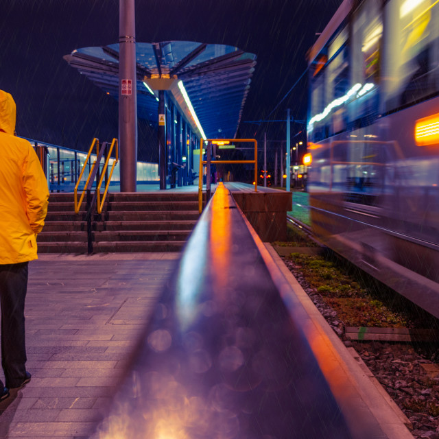 """Anonymous in the rain at Deansgate-Castlefield tram stop"" stock image"