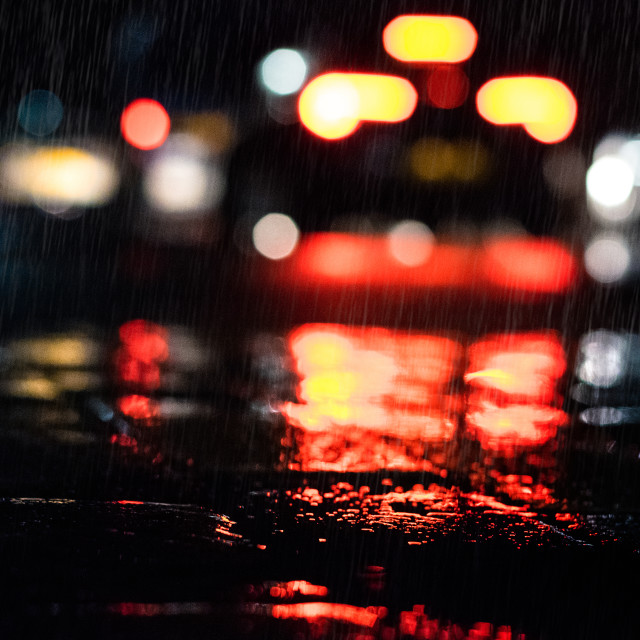 """The tail lights of passing traffic on a rain-soaked night"" stock image"