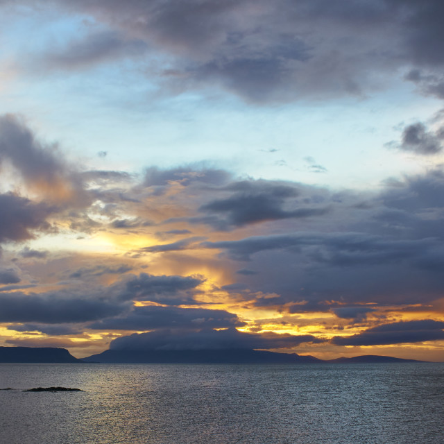 """Sunset through storm clouds over Eigg and Rum"" stock image"