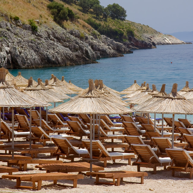"""beach couches and straw parasols ready for customers on a summer day on the adriatic coast of Albania"" stock image"