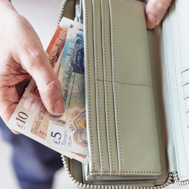 """Woman taking out pounds from her pocket wallet"" stock image"