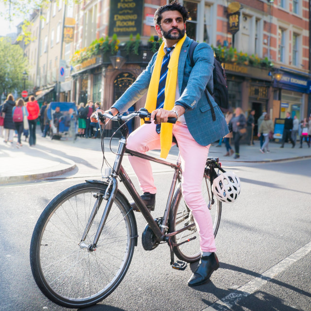 """London, UK - April 24, 2019 - street portrait of a beautifully dressed man on a bike"" stock image"
