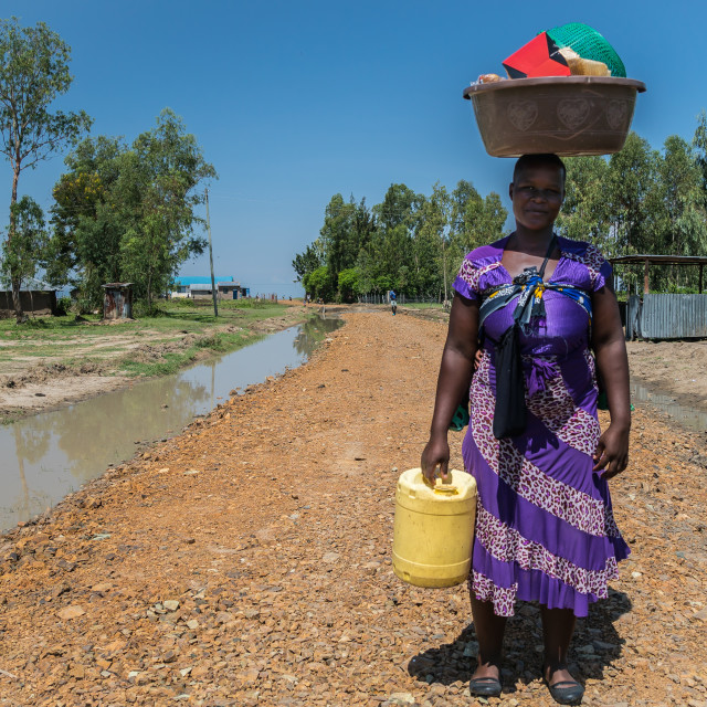 """""""near Kisumu, Kenya - March 8, 2019 - a woman carries her belongings on the top of her head"""" stock image"""