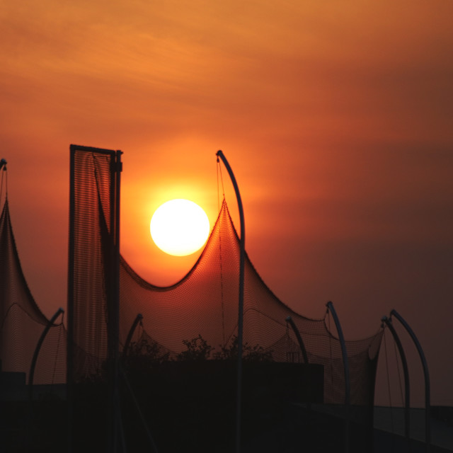 """""""A sunset in an orange sky against a silhouette of a looping mesh sports backstop"""" stock image"""