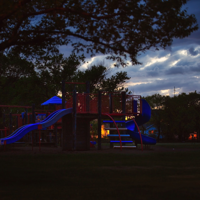 """""""An empty playground with equipment under a cloudy sky in a nightime landscape"""" stock image"""