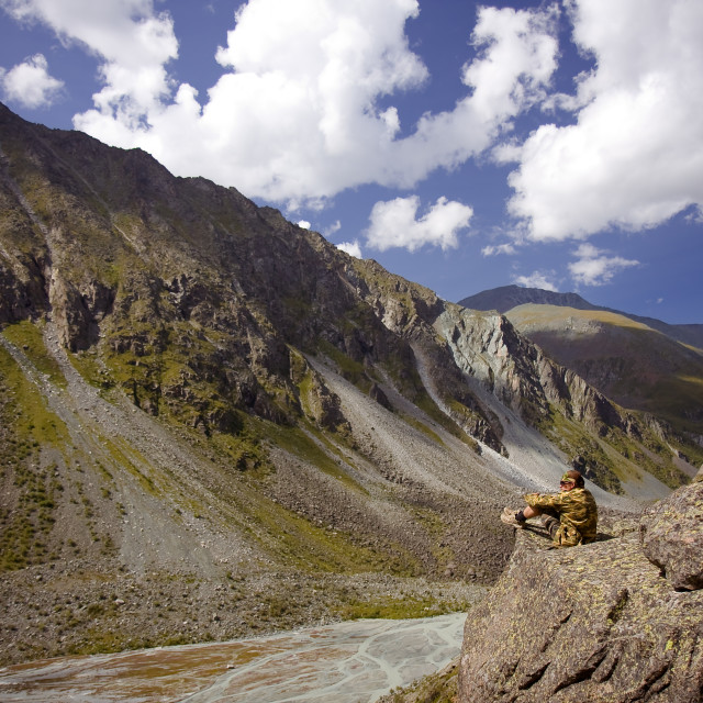 """""""Young man sits on a stone watching panorama of Altai mountains in Russia"""" stock image"""