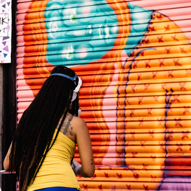 """""""Artist woman painting storefront in Malasana district in Madrid"""" stock image"""