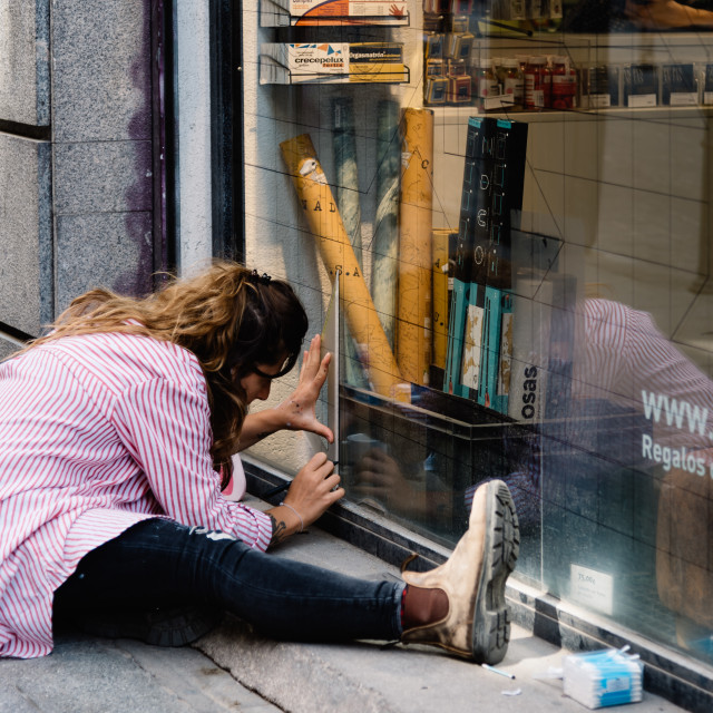 """Artist woman painting storefront in Malasana district in Madrid"" stock image"