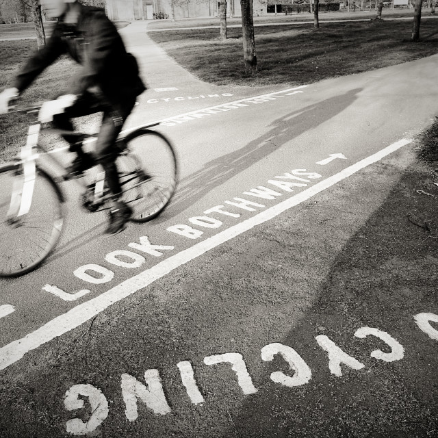 """""""black and white picture of a man riding a bicycle on a cycle path in a park in London, UK"""" stock image"""