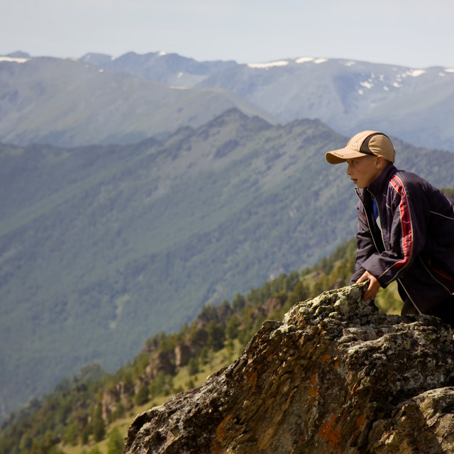 """""""Altai, Russia - August 5, 2010 - a boy, sheep shepherd's son, sits on rocks in mountains"""" stock image"""