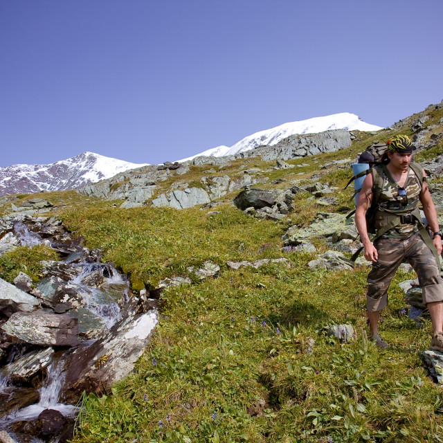 """""""young long hair man wearing camouflaged cloths walks with rucksack along a mountain river"""" stock image"""