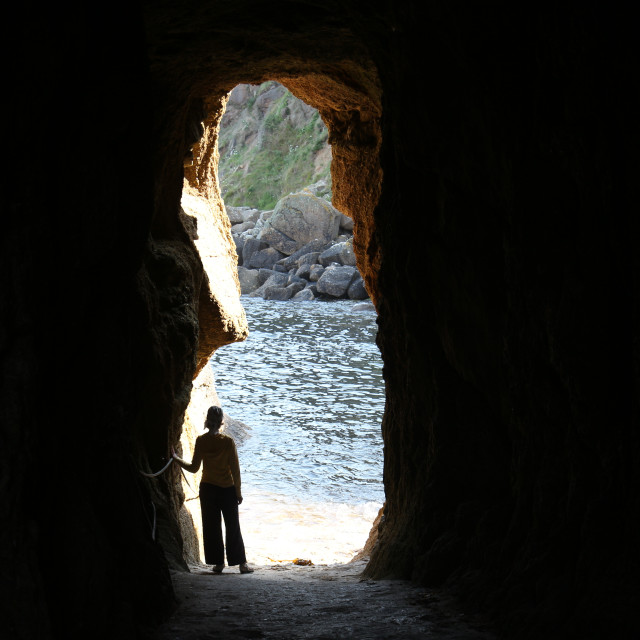 """""""a young woman stands in a dark cave and watches at a blue sea outside. Cornwall, UK"""" stock image"""