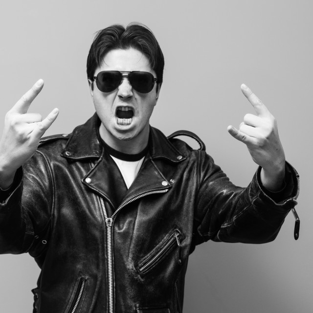"""""""black and white photo of a man wearing balck leather biker jacket screams and shows the sign of horn, traditional rock culture gesture"""" stock image"""