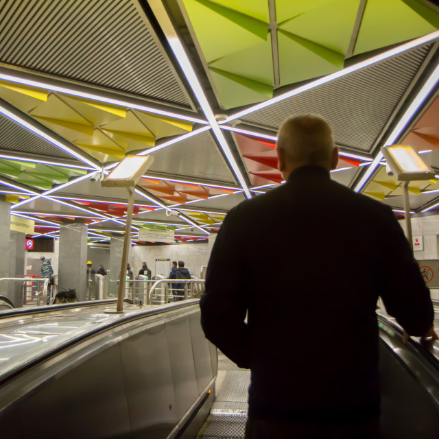 """""""October 2017 , Russia - a man on the escalator in Moscow metro looks at colourful ceiling of a station."""" stock image"""