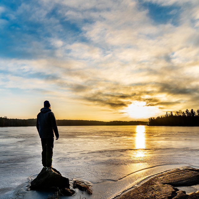 """""""Man standing by icy lake"""" stock image"""