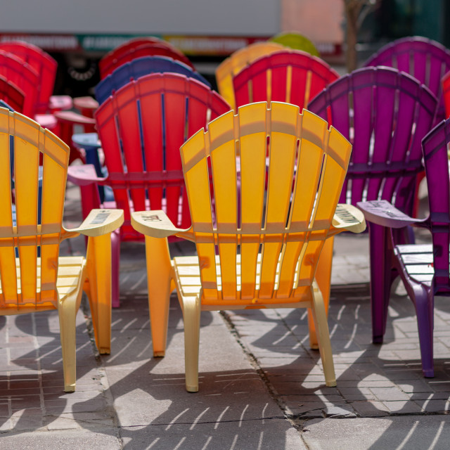 """Rows of Adirondack style chairs in the sun"" stock image"