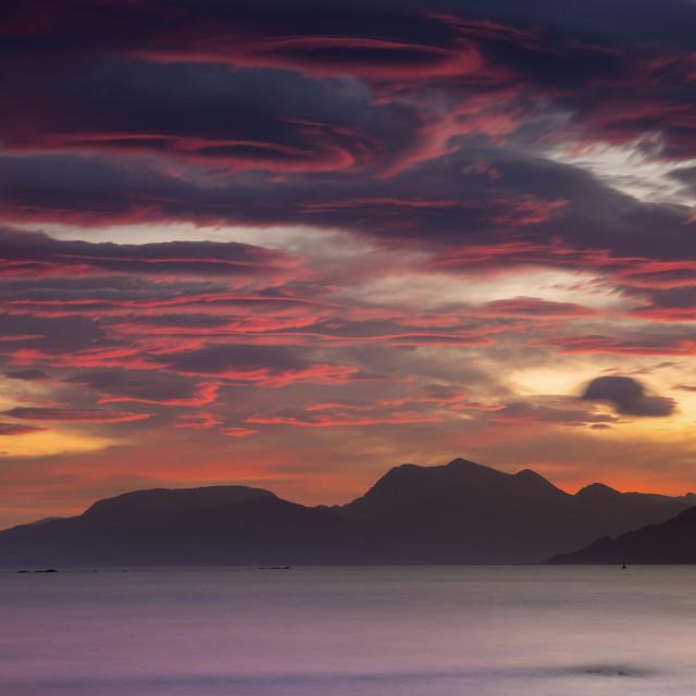 """Dramatic sunrise over sea and mountins"" stock image"