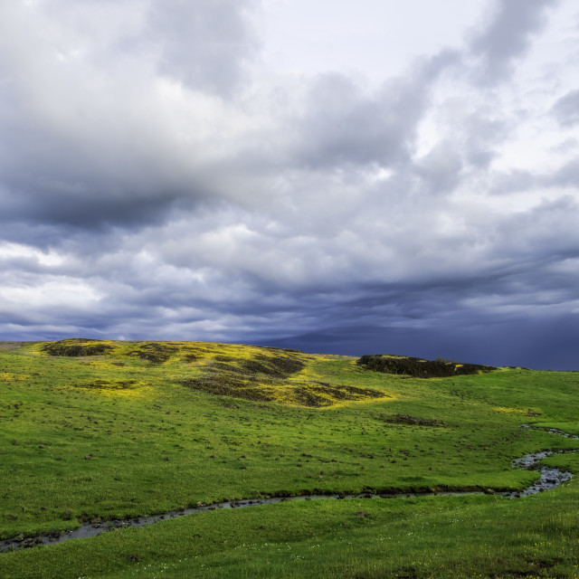 """Storm clouds passing over a beautiful green field next to a creek."" stock image"