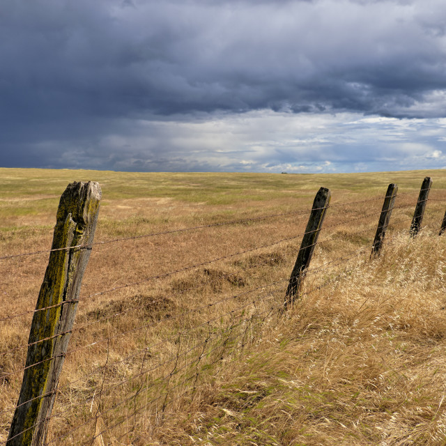 """Storm Clouds Over an Old, Wood Barbed Wire Fence on a Ranch."" stock image"