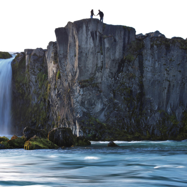 """Man and Woman Holding Hands over Godafoss Waterfall, Iceland"" stock image"