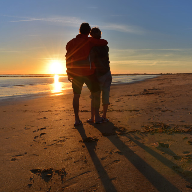 """silhouettes of a tight couple looking a beautiful sunset on the beach"" stock image"