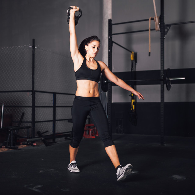 """""""Young woman realizing indoor exercises with kettlebell"""" stock image"""