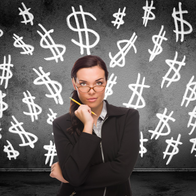 """""""Dollar Signs Drawn on Wall Behind Young Adult Woman with Pencil"""" stock image"""