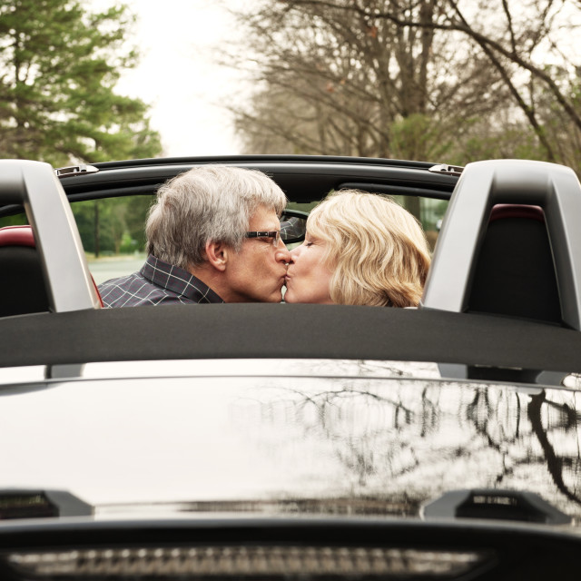 """Old Couple Kissing In Convertible"" stock image"