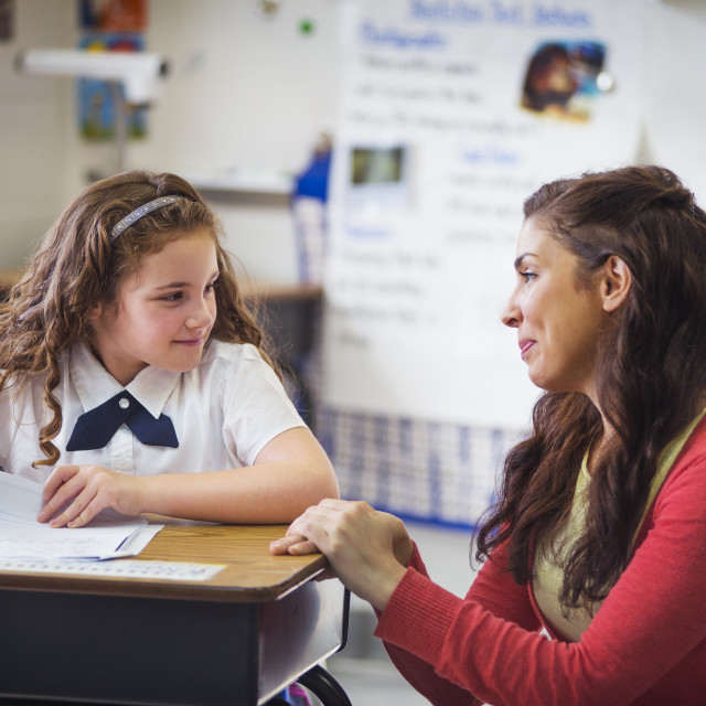 """""""Teacher Kneeling by Desk, Helping a Young Student"""" stock image"""