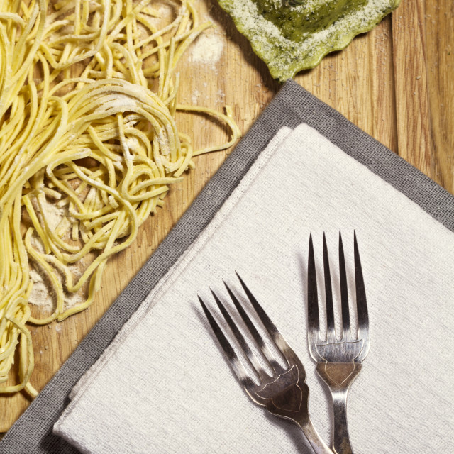 """""""Overhead view of pasta and ravioli with forks on table"""" stock image"""
