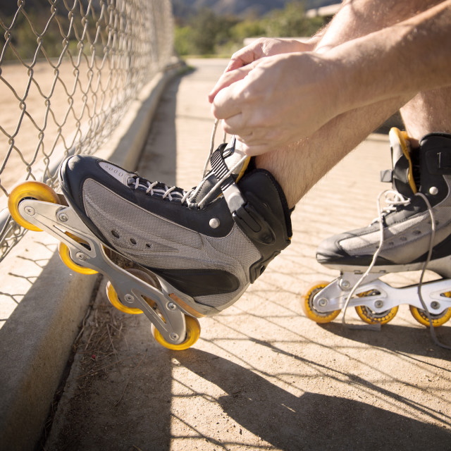 """Low section of man putting on inline skates"" stock image"