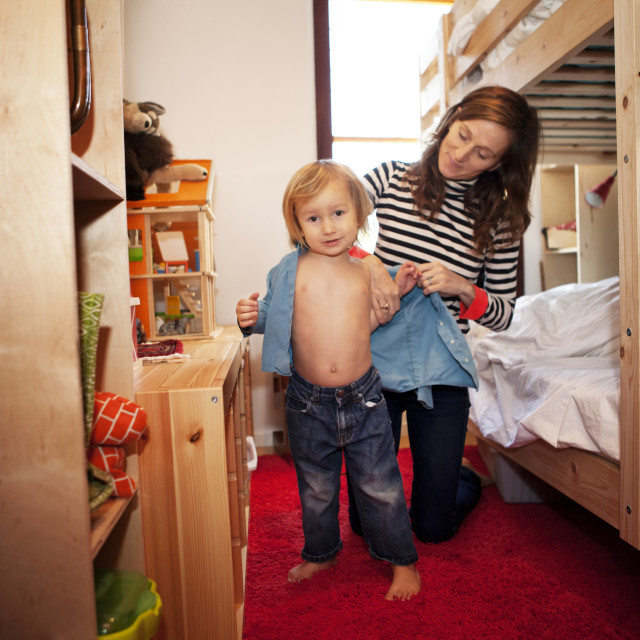 """Mother dressing son in bedroom"" stock image"