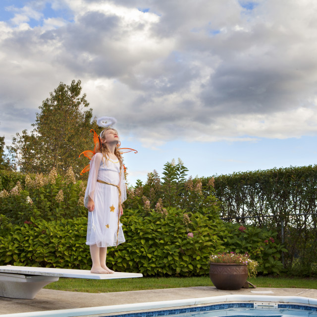 """""""Girl in fairy costume standing on diving board against sky"""" stock image"""
