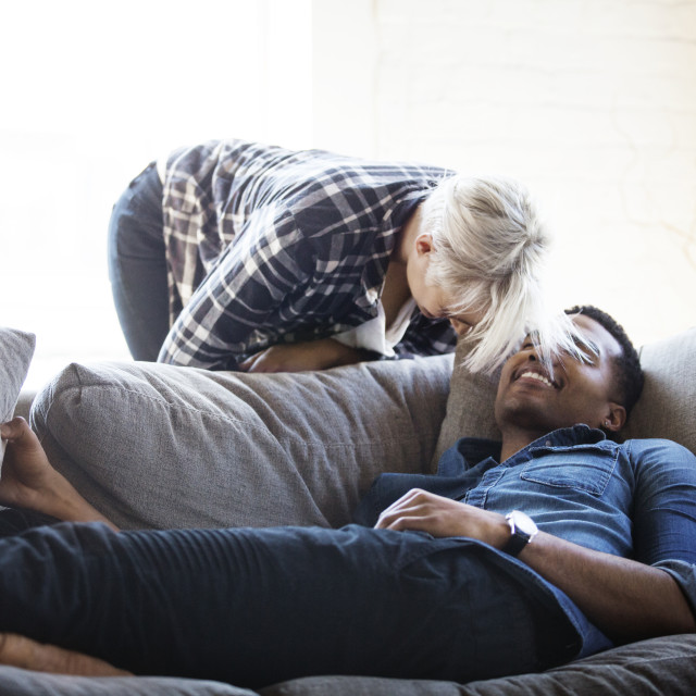 """Happy multi-ethnic couple at home"" stock image"