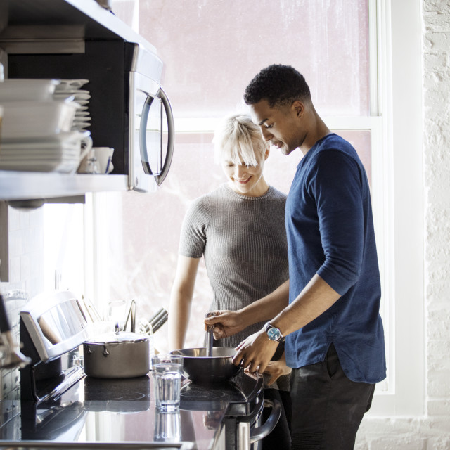 """Multi-ethnic couple preparing food in kitchen"" stock image"