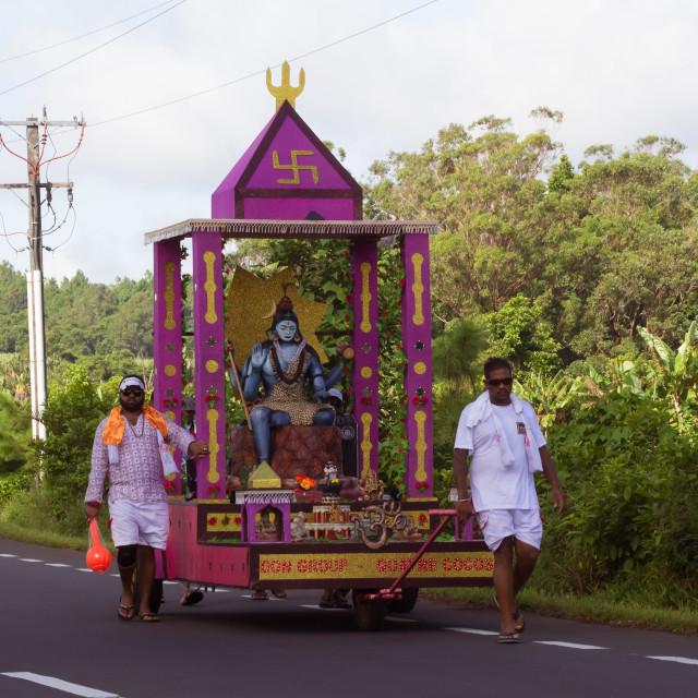 """Port Louis, Mauritius - February 11, 2018 - Men pull a cart with statue of Lord Shiva during celebrations of Hindu festival Maha Shivaratri (Great Night of Shiva)"" stock image"