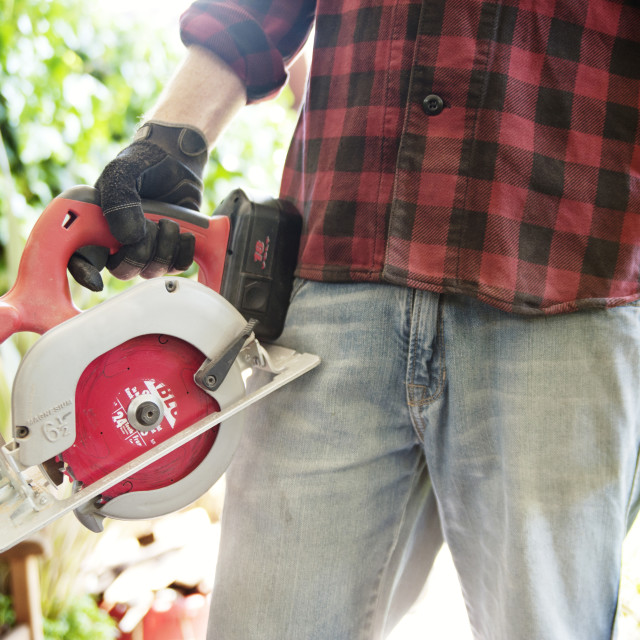 """""""Midsection of carpenter holding chainsaw"""" stock image"""