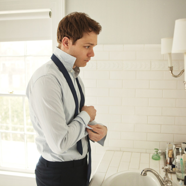 """Man Dressing in Bathroom"" stock image"