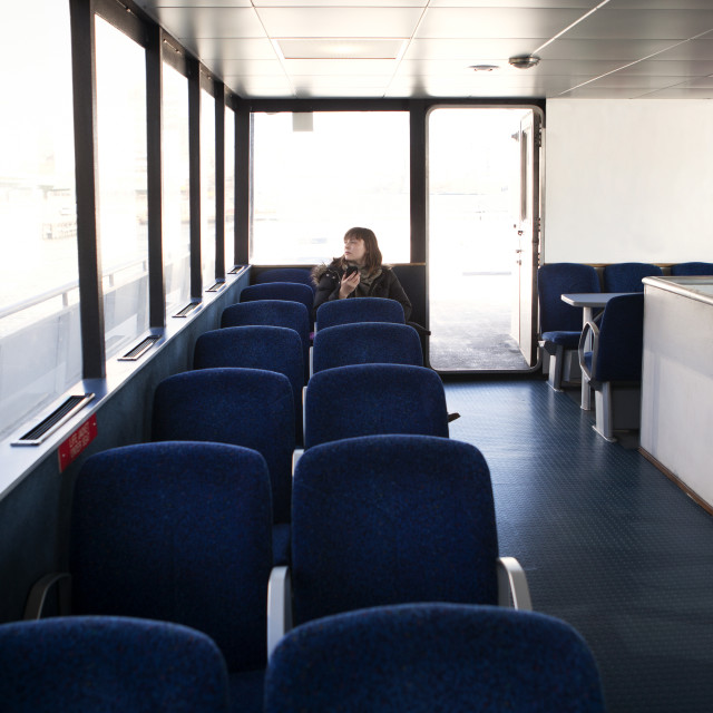 """""""Woman looking away while sitting on seat in ferry"""" stock image"""