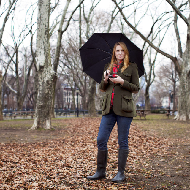 """""""Woman with umbrella looking away while holding mobile phone at park"""" stock image"""