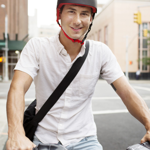 """Portrait of man riding bicycle on street"" stock image"