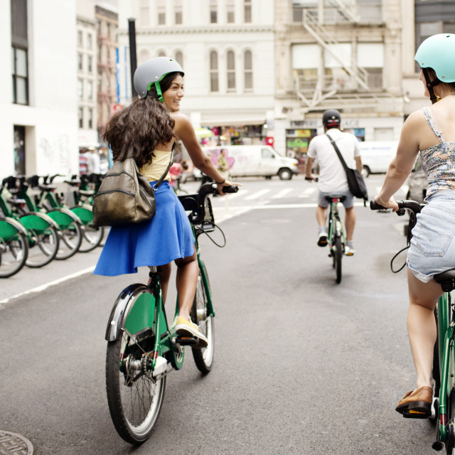 """Friends riding bicycle on city street"" stock image"