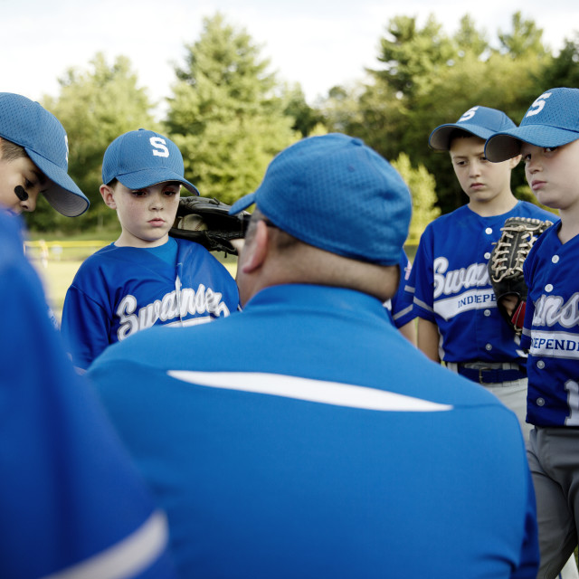 """""""Little League Team Huddling with Coach for Pep Talk"""" stock image"""