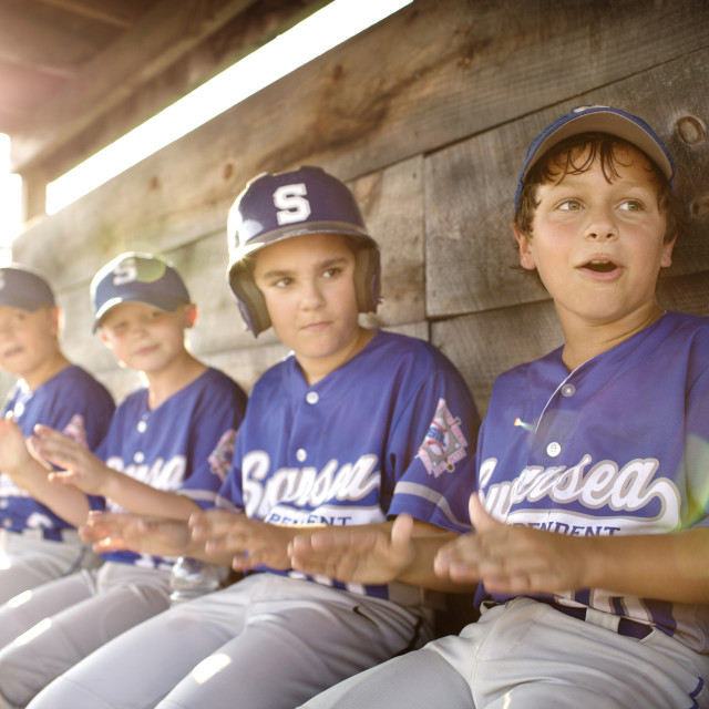 """""""Little League Team Cheering Together in Dugout"""" stock image"""