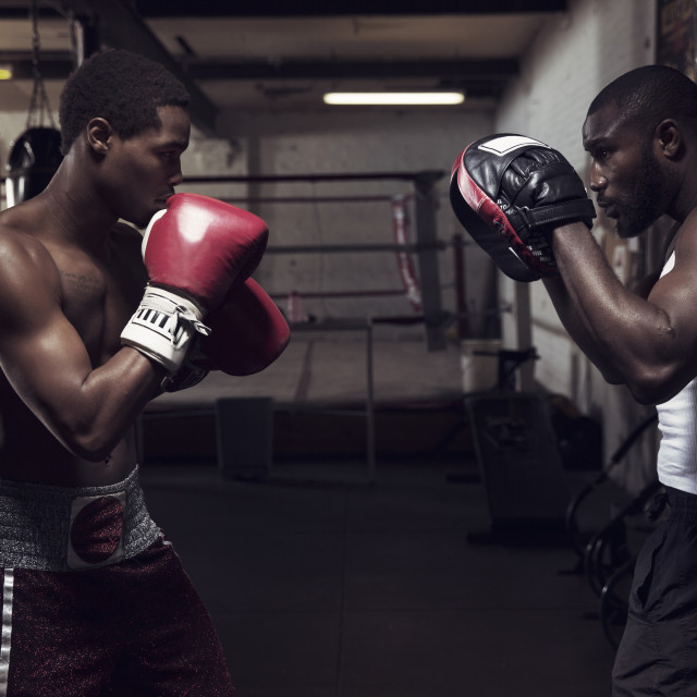 """""""Trainer with boxer practicing boxing in gym"""" stock image"""