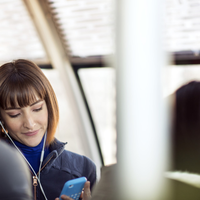 """Woman using smart phone while traveling in train"" stock image"