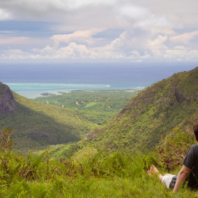 """""""A man sits on a grass and enjoys a view of the of the mountains and the ocean at the island of Mauritius"""" stock image"""
