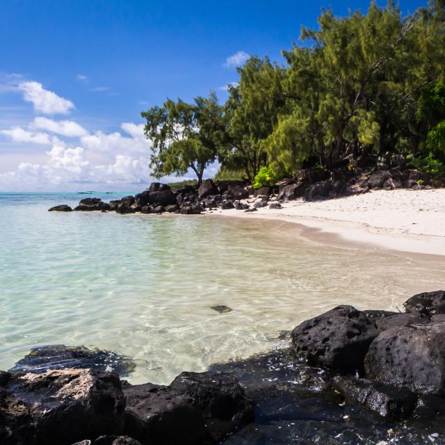 """blue ocean and black lava stones on a sandy beach of volcanic island Mauritius"" stock image"