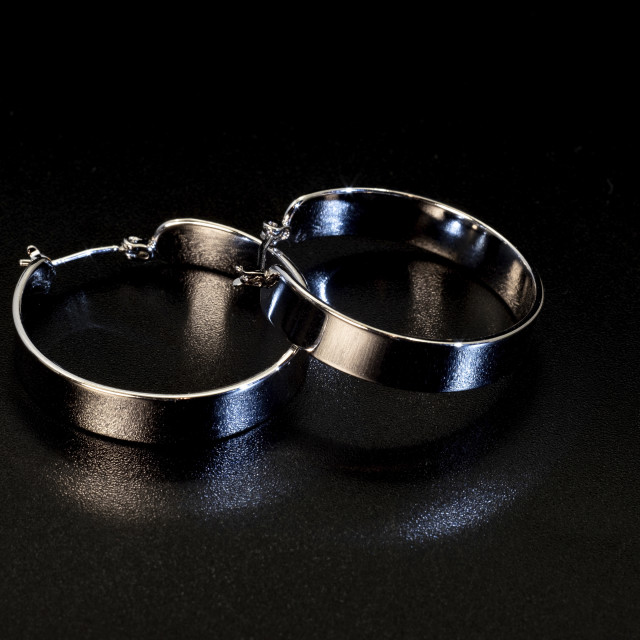 """""""Shiny round wide metal earrings on a black background."""" stock image"""
