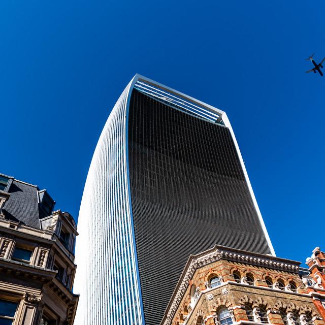 """Plane flying over skyscraper in London against sky"" stock image"